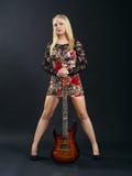 Femmina che sta con la chitarra elettrica Fotografia Stock Libera da Diritti