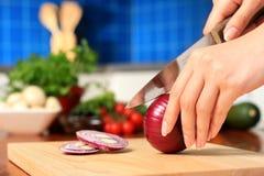 Femmina che taglia gli ingredienti a pezzi di alimento. fotografia stock libera da diritti