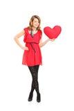 Femmina che tiene un cuscino a forma di del cuore rosso Immagini Stock