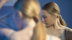 Femmina colpita che guarda sotto le ascelle nella riflessione di specchio, età di pubertà, cambiamenti del corpo video d archivio