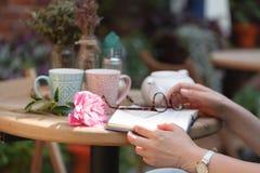 Femmina con del libro un caffè all'aperto Fotografia Stock