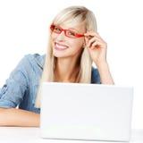 Femmina con il computer portatile che indossa le classi rosse Fotografia Stock