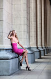 Femmina con il vestito rosa contro una colonna Fotografia Stock Libera da Diritti