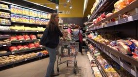 Femmina con la ragazza della figlia in pane di acquisto del carretto nel dipartimento del forno video d archivio