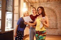 Femmina con le ragazze che leggono dalla carta Fotografie Stock