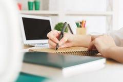 Femmina con scrittura del computer portatile in blocco note Fotografie Stock Libere da Diritti