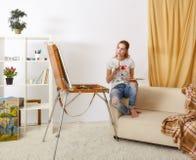 Femmina del pittore con lo sketchbook di legno che si siede sul sofà e sul painti Immagini Stock