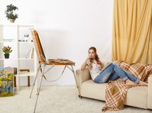 Femmina del pittore con lo sketchbook di legno che si siede sul sofà e sul painti Fotografia Stock