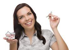 Femmina della corsa mista che presenta le chiavi e che tiene una casetta Immagine Stock