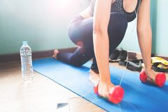 Femmina di forma fisica che allunga il suo corpo sulla stuoia di yoga, sull'allenamento e sullo stile di vita sano Fotografie Stock