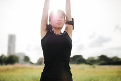 Femmina di forma fisica che allunga le mani al parco Fotografia Stock Libera da Diritti