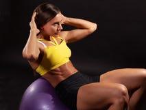 Femmina di forma fisica che fa l'ABS per esercitarsi nel fitball immagini stock