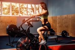 Femmina di forma fisica che per mezzo della bici dell'aria per il cardio allenamento alla palestra del crossfit Fotografia Stock Libera da Diritti