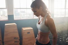 Femmina di forma fisica che prende una rottura dall'allenamento intenso alla palestra immagine stock