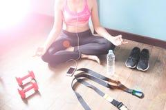 Femmina di forma fisica in pantaloni neri che allungano e che ascoltano dopo l'allenamento Fotografie Stock Libere da Diritti