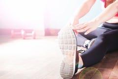 Femmina di forma fisica in pantaloni neri e scarpa da tennis che allungano dopo l'allenamento con lo spazio della copia Fotografia Stock Libera da Diritti