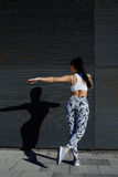 Femmina di misura in abiti sportivi che risolve mentre allungamento su fondo nero all'aperto Immagini Stock