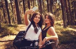 Femmina due con le biciclette che fanno selfie nella foresta di estate Immagine Stock