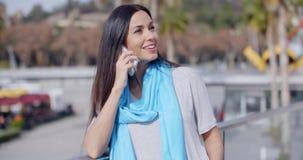Femmina entusiasta che per mezzo del telefono all'aperto archivi video