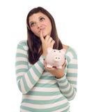 Femmina etnica che Daydreaming mentre tenendo la Banca Piggy Fotografie Stock Libere da Diritti