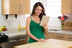 Femmina felice su lei video di sorveglianza sul suo computer della compressa mentre rilassandosi a casa con il sorriso perfetto Immagini Stock