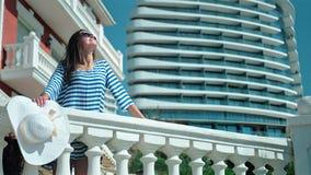Femmina felice in vestito ed occhiali da sole a strisce che gode e che sorride sul terrazzo di bella costruzione stock footage