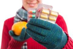 Femmina fredda che mostra le pillole contro il concetto naturale delle vitamine immagine stock