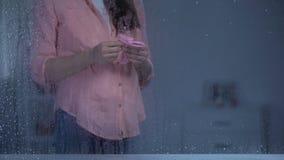 Femmina incinta che mette i calzini rosa del bambino sulla pancia, aspettativa della ragazza, giorno piovoso archivi video