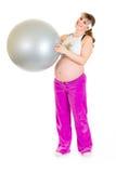 Femmina incinta nella sfera di forma fisica della holding degli abiti sportivi Immagini Stock