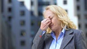 Femmina invecchiata nella tensione ritenente degli occhi del vestito, disagio della menopausa, pressione sanguigna stock footage