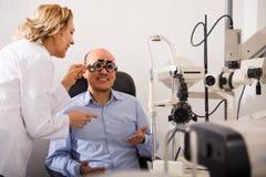Femmina matura dell'oftalmologo e vista maschio del controllo del pensionato in clinica fotografia stock