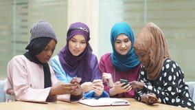 Femmina musulmana di giovani affari delle coppie facendo uso del contatto dello Smart Phone con il partner video d archivio