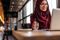 Femmina nel hijab al caffè che ha videoconferenza sul suo computer portatile fotografie stock libere da diritti