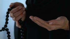 Femmina nel hijab che conta le preghiere dal rosario a disposizione, dalla fede e dalla religione, primo piano stock footage