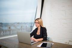Femmina nell'introduzione fiera dell'imprenditore di vetro sul NET-libro portatile Facendo uso di netbook Fotografia Stock Libera da Diritti