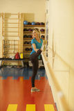 Femmina nella classe variopinta di forma fisica con un corrimano della gamba, Fotografie Stock