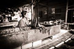 Femmina non identificata che vende i pesci della griglia Fotografie Stock