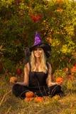 Femmina piacevole nell'yoga di pratica del costume della strega Fotografia Stock