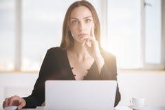Femmina premurosa che per mezzo del computer portatile Fotografia Stock