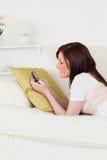 Femmina red-haired sveglia che scrive un testo sul suo telefono Fotografie Stock Libere da Diritti