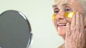 Femmina senior con le toppe antinvecchiamento dell'occhio dell'idrogel sul fronte che guarda in specchio archivi video