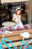 Femmina sorridente attraente nella seduta bianca in caffè con i fiori accanto alla sua bici blu fotografie stock