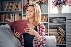 Femmina sorridente che tiene un libro Immagini Stock