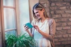 Femmina sorridente dei giovani che per mezzo del dispositivo digitale della compressa Fotografie Stock Libere da Diritti