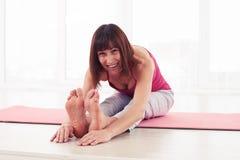 Femmina sorridente del positivo nella tenuta di andata messa di posa di yoga della curvatura Immagine Stock