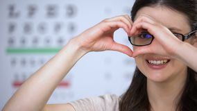 Femmina sorridente in vetri che fanno cuore delle mani, buona qualità dei servizi, cura archivi video