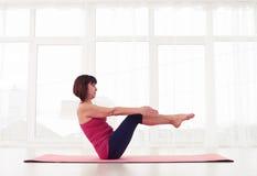 Femmina sportiva che lavora l'ABS laterale in una palestra su una stuoia di yoga fotografia stock libera da diritti