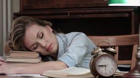 Femmina stanca che prende un pelo su un mucchio dei libri e che è svegliato da un allarme Fotografia Stock