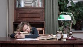 Femmina stanca che prende un pelo sul mucchio dei libri nel suo luogo di lavoro e che sono svegliati da un allarme Immagini Stock