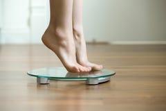 Femmina sulle punte dei piedi che stanno sulle bilancie Fotografia Stock Libera da Diritti
